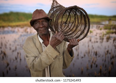 NKHOTAKOTA, MALAWI - JUNE 14, 2018: Unidentified fisherman carries a fish trap on the waterfront of Lake Malawi. Malawi is one of the poorest countries in the world.