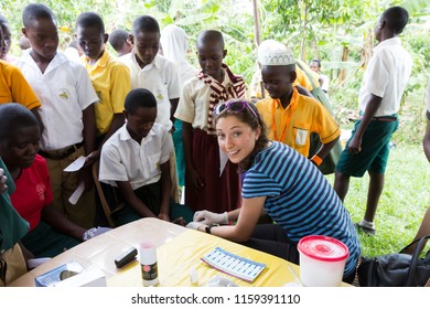 Nkokonjeru, Uganda. June 22 2017. A young white (Caucasian) woman testing a Ugandan boy for HIV by pricking his finger and drawing blood into a capillary tube.