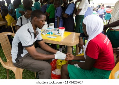 Nkokonjeru, Uganda. June 22 2017. A young man testing a girl for HIV by pricking her finger and drawing blood.