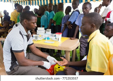 Nkokonjeru, Uganda. June 22 2017. A young man testing a boy for HIV by pricking his finger and drawing blood.