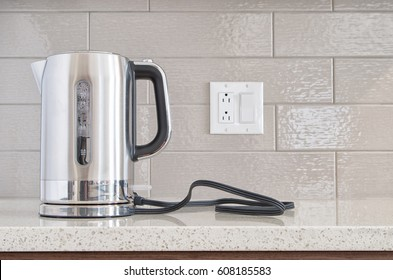 nnModern electric stainless steel kettle sitting on its base on a granite counter top against a ceramic background