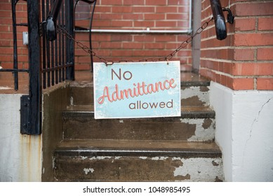no admittance allowed sign hanging on chain at city restaurant in rain