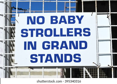 No baby strollers in grand stand sign displayed outdoors.