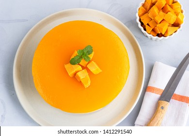 No Bake Mango Cheesecake on a White Plate and on White Background Garnished with Mint Leaves, Directly from Above  Photo. Mango Mousse, Mango Dessert Photography.