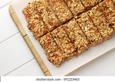 No baking granola bars on white wooden table. Healthy food for diet.