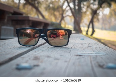 No brand sunglasses in park sitting on wood bench.