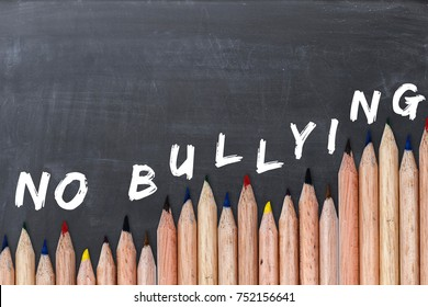 No bullying text on chalkboard with colorful pencils as border