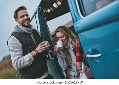 No cares and no rush.  Beautiful young couple having hot drinks and smiling while enjoying their road travel