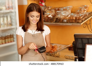 No cash needed. Beautiful female baker swiping a credit card in her own bakery processing payment
