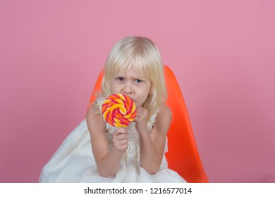No child can resist these exciting yummy treats. Small girl hold lollipop on stick. Small child with sweet lollipop. Happy candy girl. Happy childhood food.