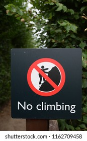 No climbing red and white warning sign on a black background with symbol of man climbing with shallow depth of field showing foliage.