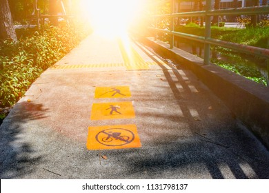 No Cycling sign , Walk sign and blind walking sign painted on the road with warm light.