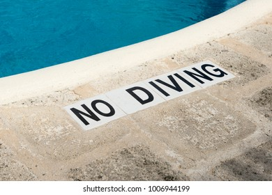 """No Diving"" sign along the edge of a swimming pool"