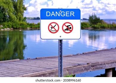 No diving no swimming danger sign    on pier waterfront to warn people. It's dangerous to swim dive in unsupervised water due to shallow water, underwater logs or big rocks can cause serious injury.