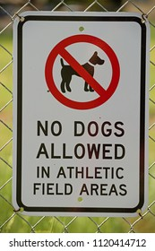 no dogs allowed in athletic field areas sign on a chain link fence