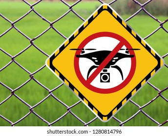 No drone zone Warning sign at fence wall, Prohibition sign to fly with drones on the net fence. No drone zone, No drone flying at perimeter fence netting of airport airspace or Detention Center