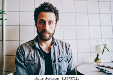 No emotion face of bearded hipster guy sitting indoors in cafe. Close up portrait of creative graphic designer dressed in denim wear looking at camera. Lost look, and uncertainty