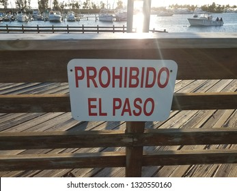 no entrance prohibido el paso sign on wood fence with water and boats