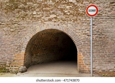 No entrance for segway sign in front of old brick wall with tunnel