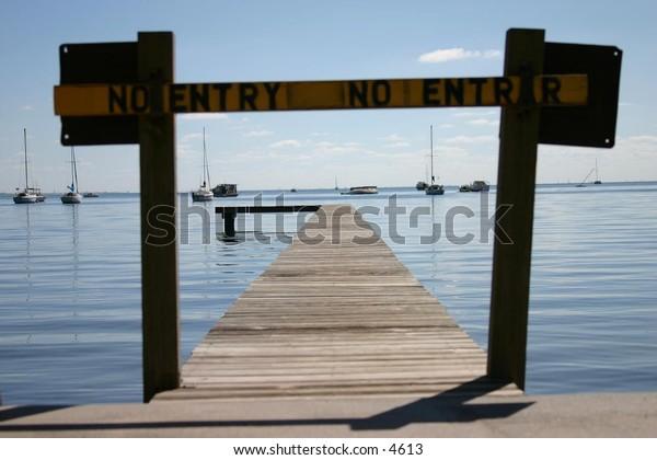 no entry sign and blockade along pier