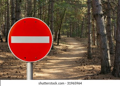 No entry sign in front of a forest path representing environmental protection