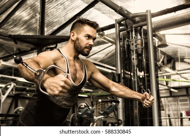 No excuses in sports. Low angle shot of a strong young fit and toned muscular athletic man doing chest exercise using cable crossover machine gym sports fitness motivation strength concept copyspace