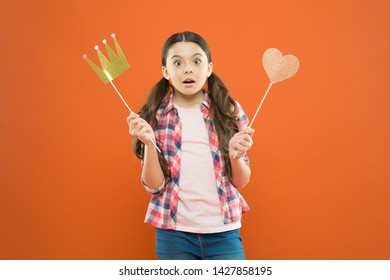With no expectation of reward. Little girl holding prop crown and heart on stick as favorite reward. Cute mini miss beauty pageant winner enjoying reward for success. Awarding with prize and reward.