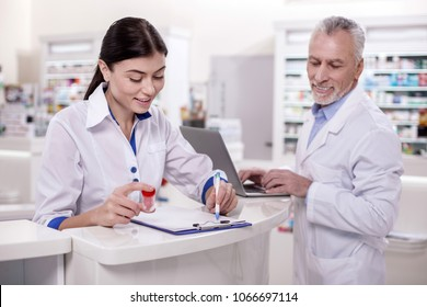 No experience. Positive female pharmacist taking notes while mature male doctor using laptop