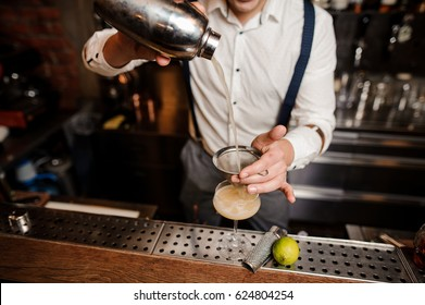no face bartender is pouring coctail into the glass at the bar stand
