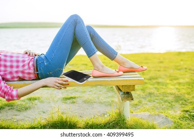 No face. caucasian girl, Woman lie on bench against green fresh grass, sea and sunset sky background . Female on nature spring backdrop. Slim legs in jeans