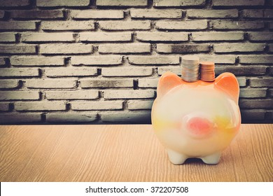 no face piggy bank on perspective floor with old dirty brick wall