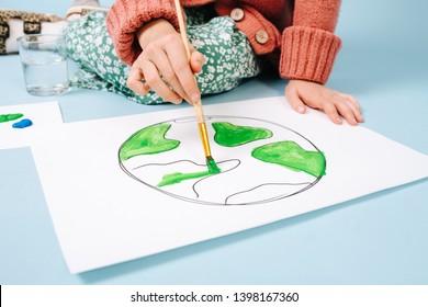 Kein Gesichtsporträt von Teenagermädchen, die Erde auf dem Papier malen. gekropft. Sie benutzt grüne Farbe auf einem Pinsel.