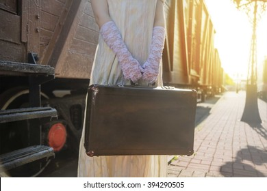 no face. Woman with suitcase stand on stair of wagon. Railway station against retro vintage old locomotive in perspective.Young adult girl hold in hands case. Female wear gloves and dress