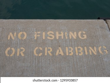 """""""No Fishing or Crabbing"""" Sign Painted on a Concrete Quayside in the Seaside Town of Padstow on the South West Coast Path in Rural Cornwall, England, UK"""