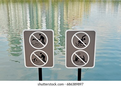No fishing and no swimming sign next to a pond in the park