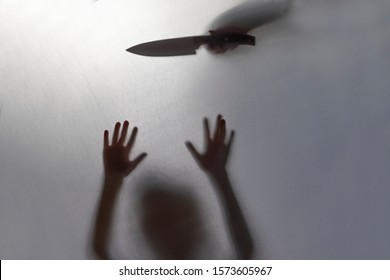 no focus. the fabric behind her. silhouette and shadow. baby knife over his head. domestic violence concept