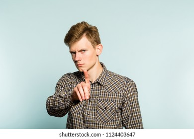 no. forbidden. don't do it. serious frowning man hand gesture. portrait of a young guy on light background. emotion facial expression. feelings and people reaction.