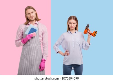 No gender stereotypes. Pretty young woman lifting up a screw gun and posing with it while her boyfriend holding sponges and wearing an apron