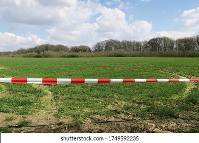 no go area: a landscape behind white and red barrier tape