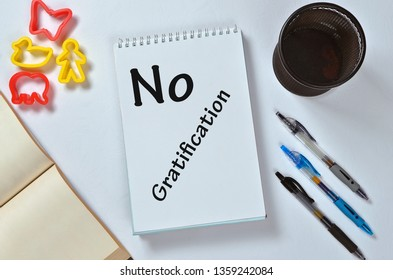 No gratification text on notepad with office accessories. Business motivation, inspiration concepts, pen and pencil case, yellow plastic duck toy and person toy, red butterfly toy and red elephant toy