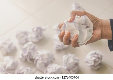 No idea and fail concept - Human hand holding crumpled paper or trash and white paper ball and waste on the floor, A hand are crumpling a paper, Recycling or fail creativity concept.