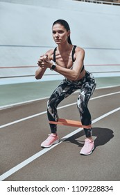 No ifs or buts to workout. Beautiful young woman in sports clothing crouching using resistance band while standing on the running track outdoors
