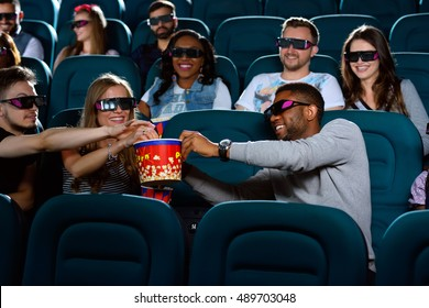 No joy without the right snack. Shot of a cheerful young African man sharing his popcorn with his friends at the movie theatre holding out his popcorn bucket