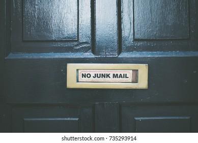 No Junk Mail message on a golden metal plate on a dark wooden door