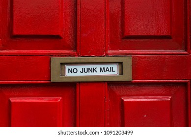 no junk mail sign on letterbox of red wooden door