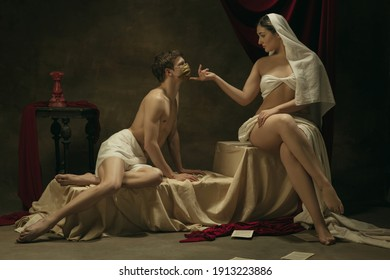 No kisses with golden face mask. Modern remake of classical artwork with coronavirus theme - young medieval couple on dark background, golden colored. Concept of coronavirus, pandemic, creativity.