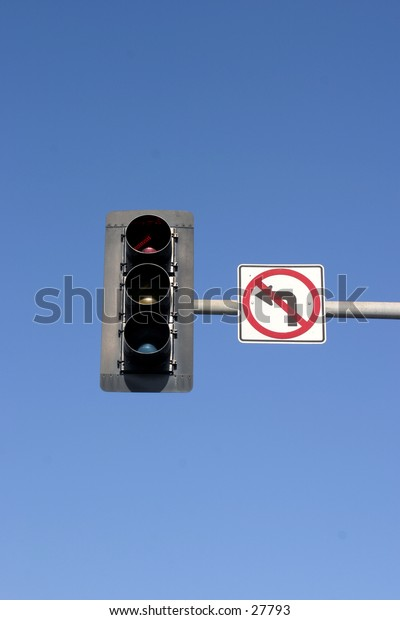no left turn sign attached to a traffic light with a blue sky background