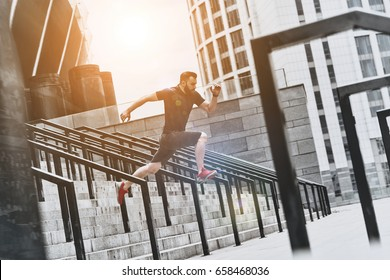 No limits. Full length of handsome young man in sport clothing jumping while exercising outside