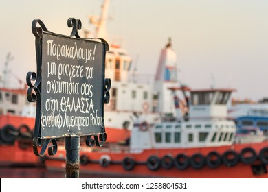 A No Littering signboard writen in Greek (Please, dont throw garbage to the sea) placed at the waterfront of Rhodes, Greece.