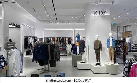 No logo. Inside a retail shop selling fashion clothing for adults and kids with mannequin. Wide angle shot